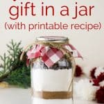 A gift jar filled with homemade brownie mix with a decorative check fabric lid