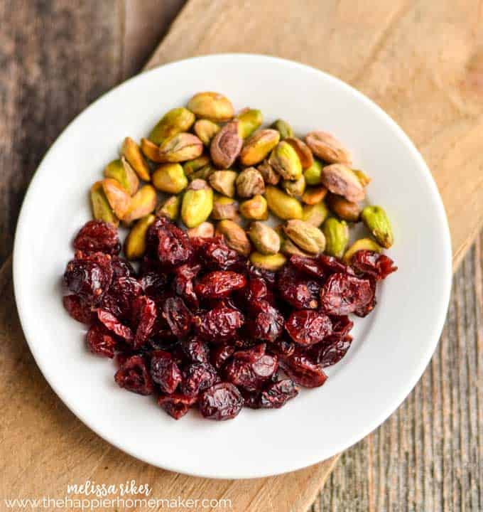 A plate filled with Pistachios and cranberries