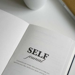 "An open book that has ""self journal"" on the title page"