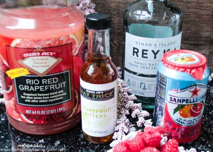 A collection of ingredients to make ruby red raspberry cocktail including bitters, red grapefruit and raspberries