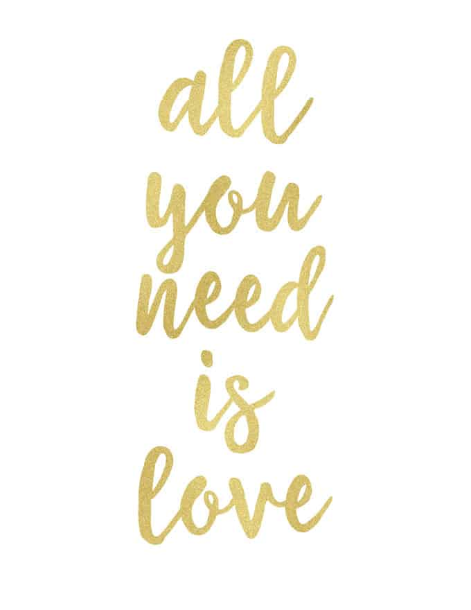 """The words \""""all you need is love\"""" written in gold cursive"""