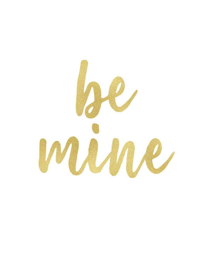 "The words ""be mine"" written in gold cursive"