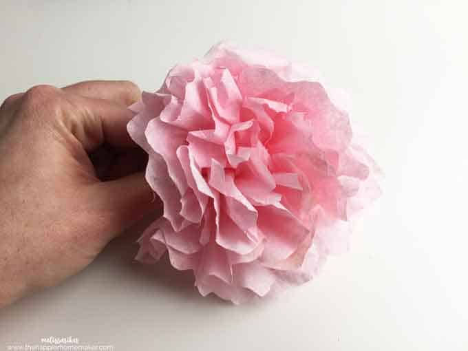 A pink coffee filter flower being shaped by a left hand