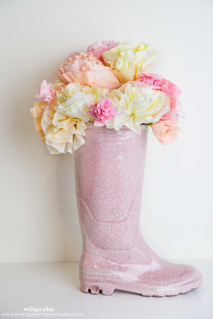 A pink wellie boot vase filled with pink pink and white coffee filter flowers