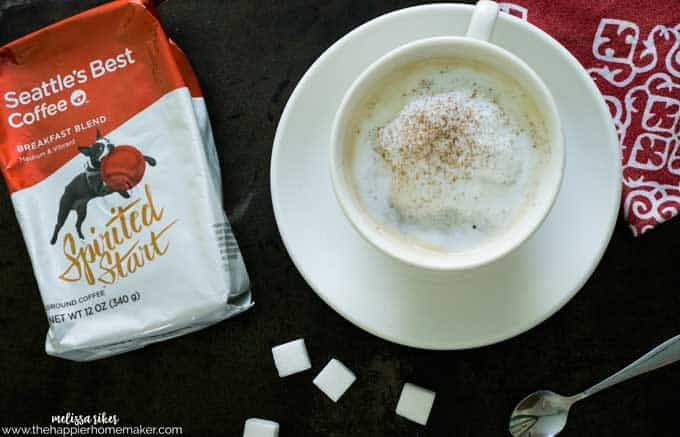 An above picture of a cup of coffee with cream and garnished with sugar cubes