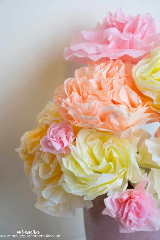 A close up of a collage of orange, yellow and pink coffee filter roses