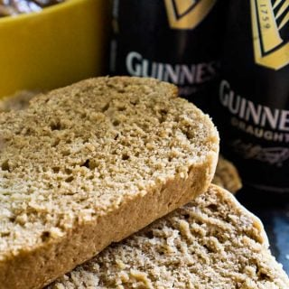 A close up of Guinness beer bread with two cans of Guinness in the background