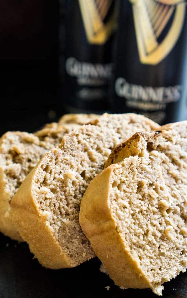 A close up of three slides of Guinness beer bread with two cans of Guinness in the background