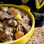 A yellow bowl full of Guinness Irish Beef Stew with two Guinness cans in the background