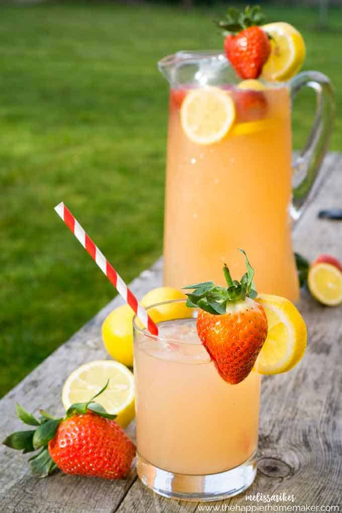A close up of a cup of strawberry lemonade with fresh strawberries, slices of lemons and a red/white straw