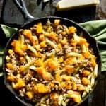 A cast iron pan filled with butternut squash and sausage penne