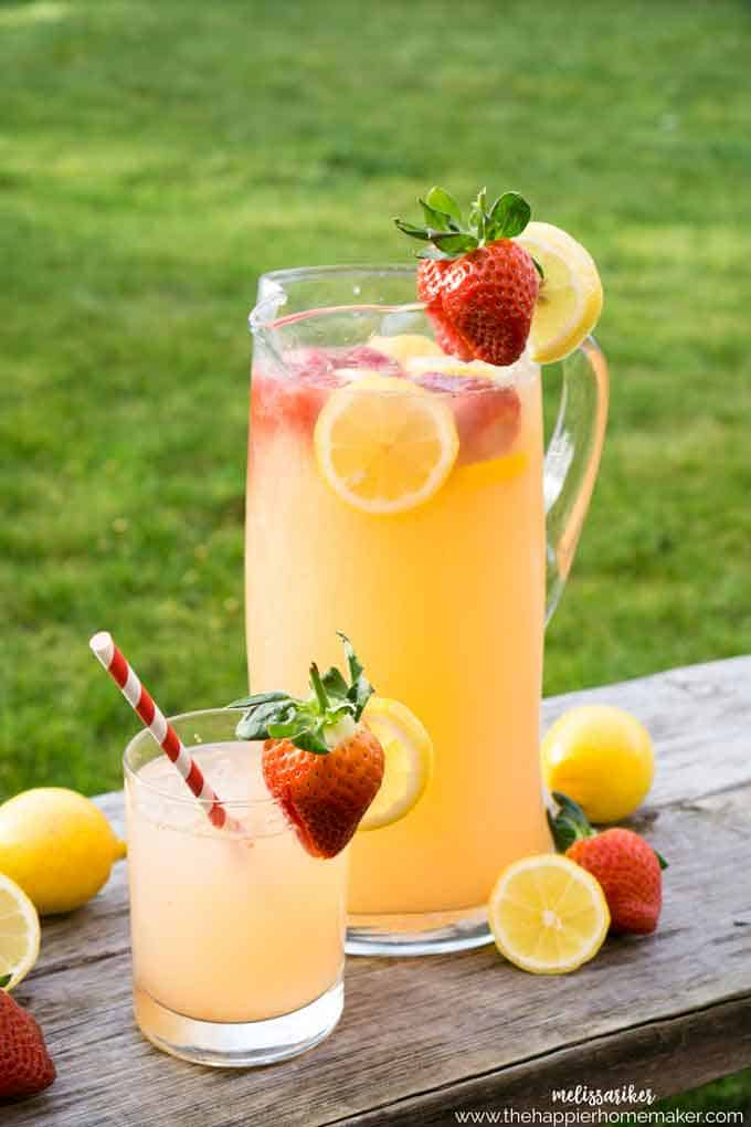 A pitcher of strawberry lemonade with fresh lemons and strawberries sitting on a wood table outside with a glass of lemonade next to it