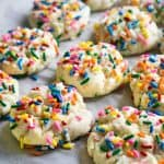 close up of funfetti cookies with colorful sprinkleson parchment paper