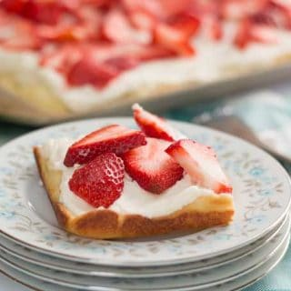 A close up of a slice of strawberry cream puff cake on a plate, topped with strawberries