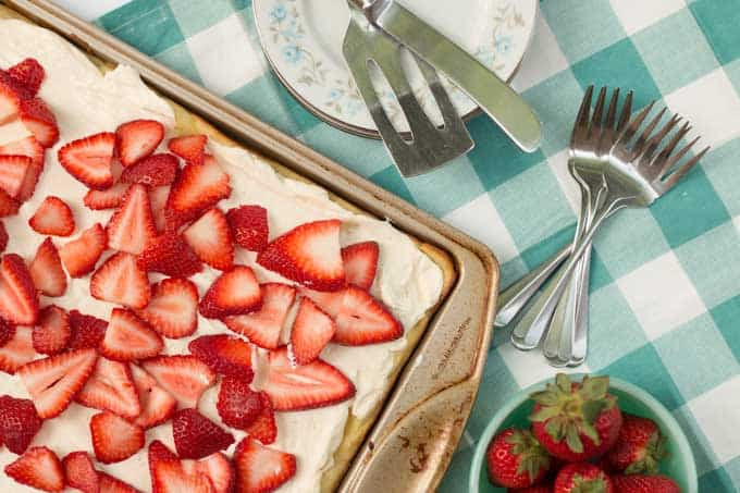A cade in a baking pan topped with cream puff and fresh, sliced strawberries with silverware next to the baking pan
