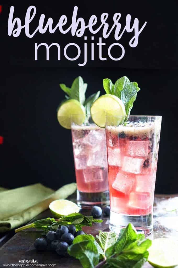 Two blueberry mojitos garnished with limes