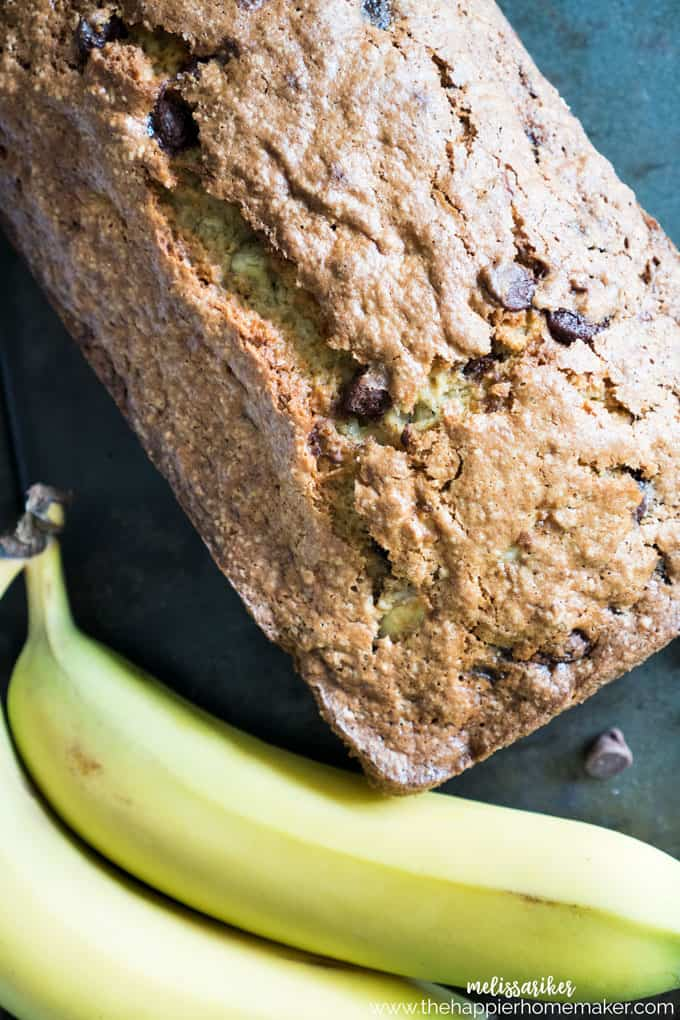 A close up of a loaf of chocolate chip banana bread on a table next to two bananas