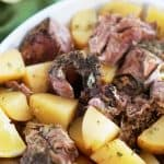 Easy Slow Cooker Greek Leg of Lamb in the Slow Cooker - fall off the bone tender lamb with perfectly roasted lemon potatoes all made in the crock pot!