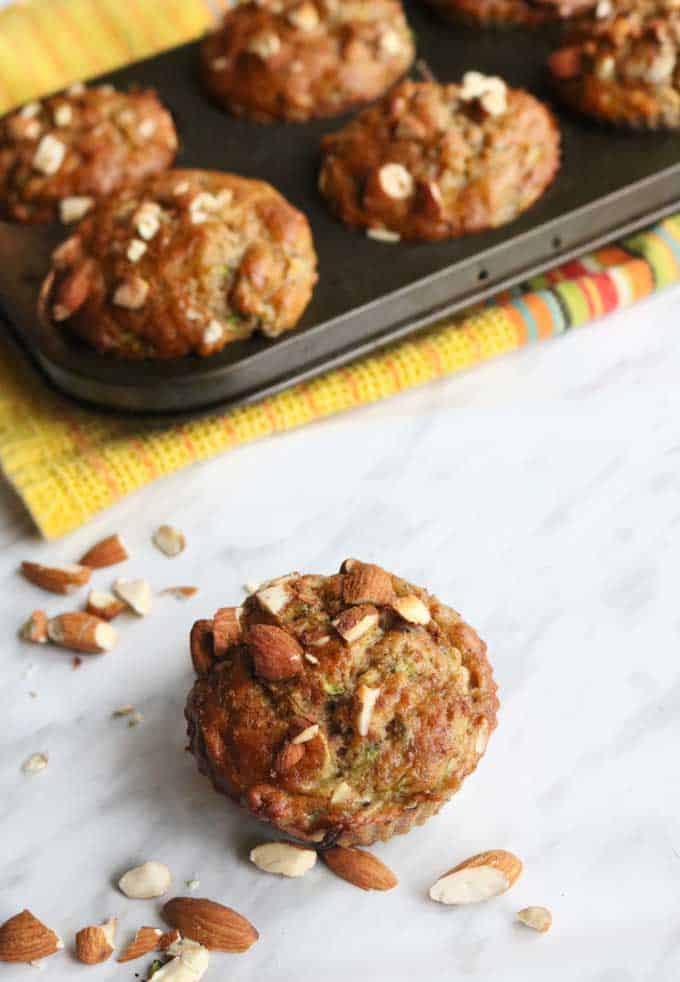 A close up of almond banana zucchini muffins on white paper next to a tray of muffins