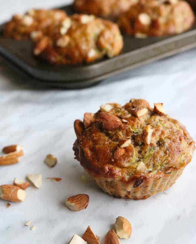 A close up of almond banana zucchini muffins on white paper