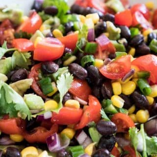 A close up of cowboy caviar made of black beans, corn salad, cilantro and lime