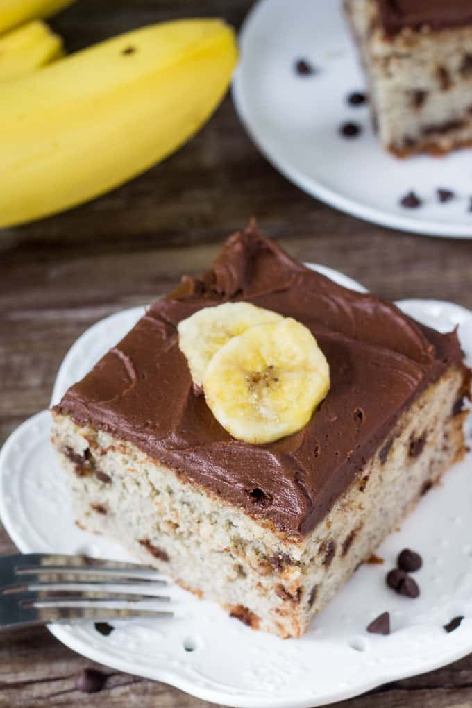A piece of chocolate chip banana cake with chocolate frosting and slices of fresh banana on top.