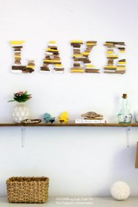 Perfect for the lake house! Learn how to make this DIY painted driftwood lake sign. A fun and easy beach decor idea.