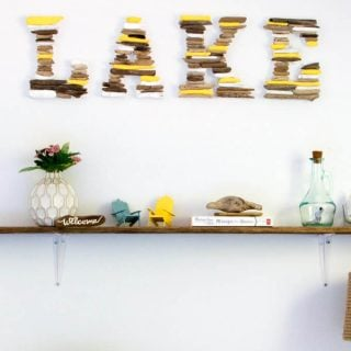 DIY decor spelling LAKE above a wooden shelf with small decor pieces on it