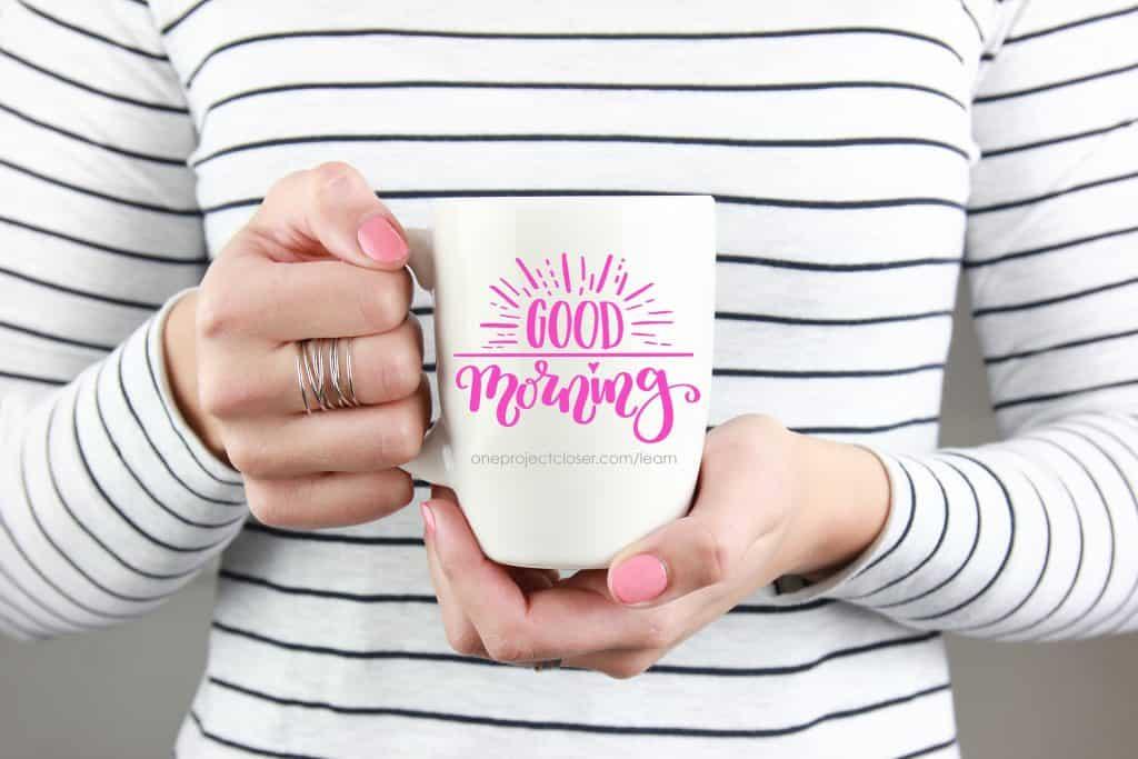 hand holding hand lettered coffee mug