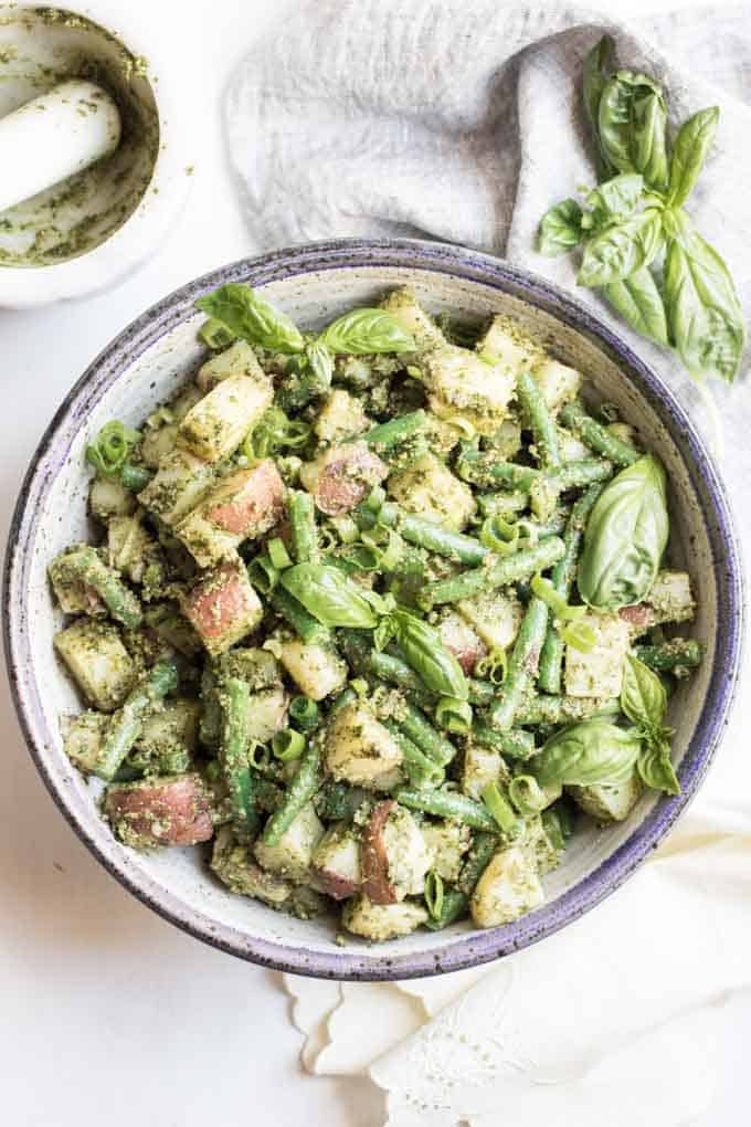 A bowl of pesto potato salad with green beans.