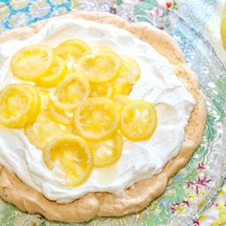 An in-process picture of candied lemon pavlova with fresh whipped cream