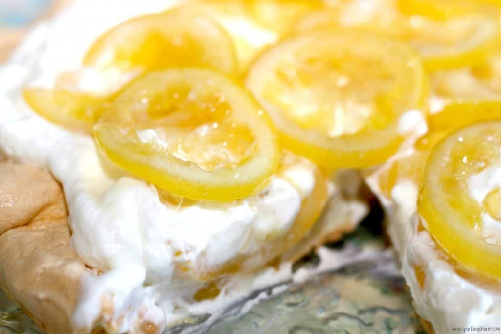 A close up of candied lemon pavlova on whipped cream