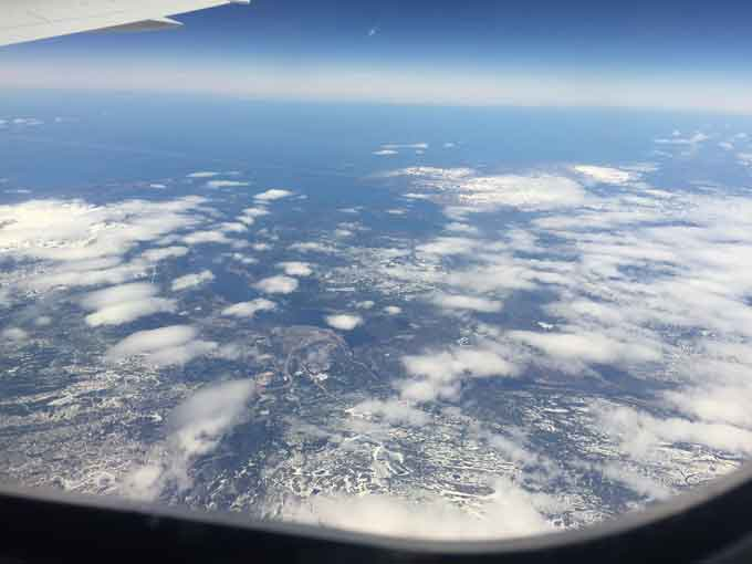 A picture of the earth taken from a plane showing clouds and water.