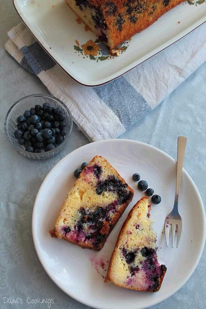 Two slices of blueberry lemon basil cake on a white plate with silver fork garnished with four blueberries