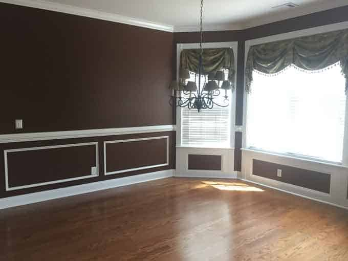 A large empty dining room with maroon paint