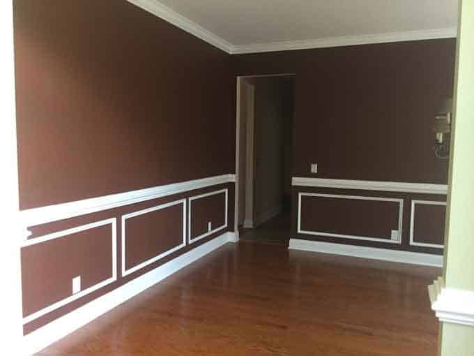 An empty room painted dark brown with white molding trim