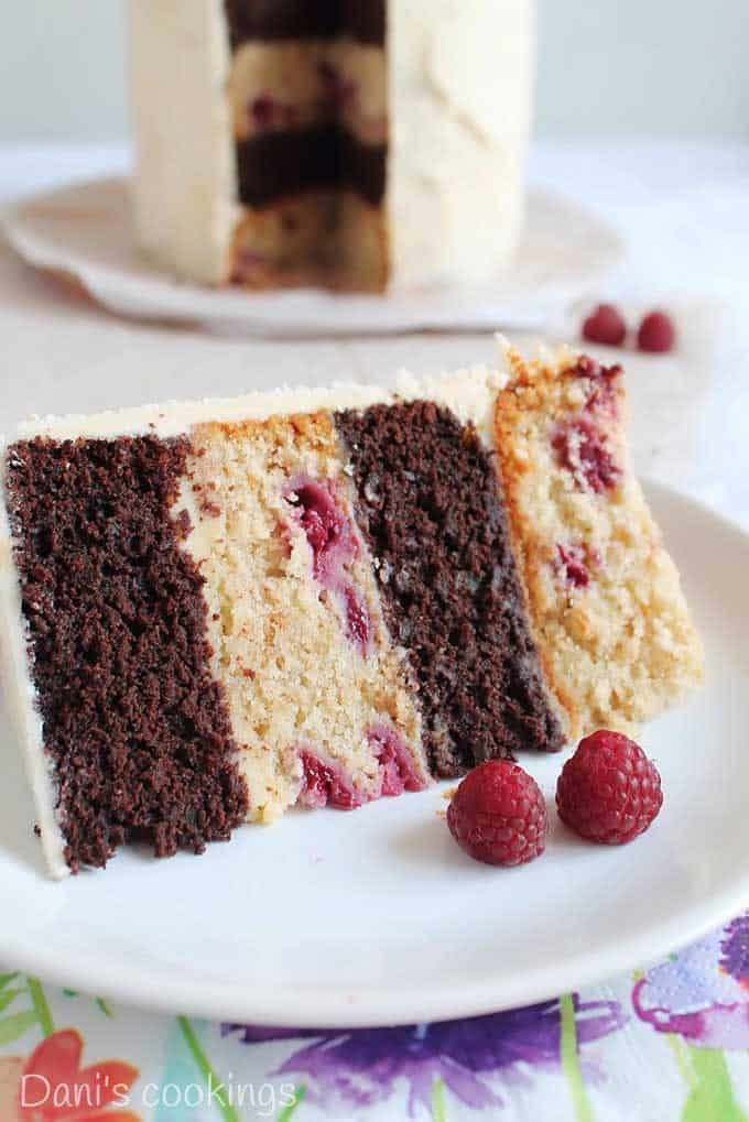 A close up of a slice of four layer raspberry chocolate cake on a plate garnished with two fresh raspberries
