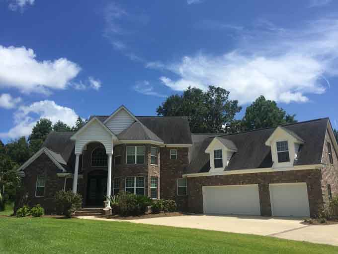 large brick home with two story arched entryway and three car garage