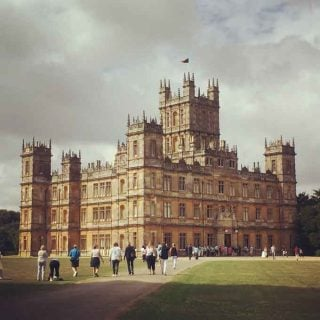 A large clock tower towering over Highclere Castle
