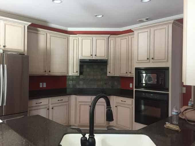 A red kitchen with off white cabinets and dark appliances