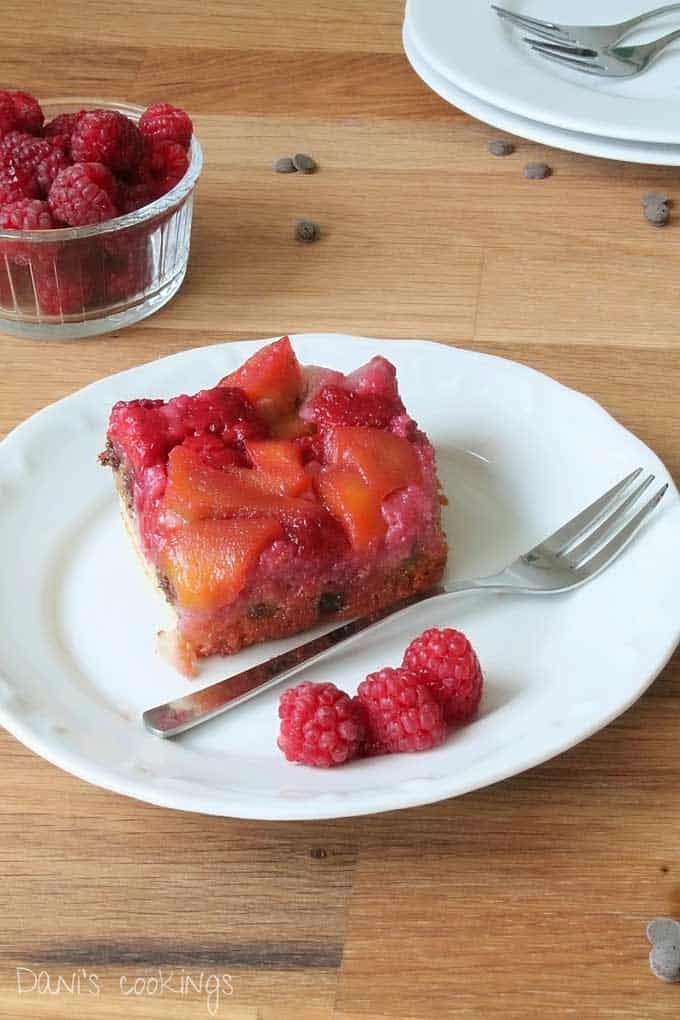 A plate of food with a slice of raspberry upside down cake on a table with a silver fork garnished with three fresh raspberries.