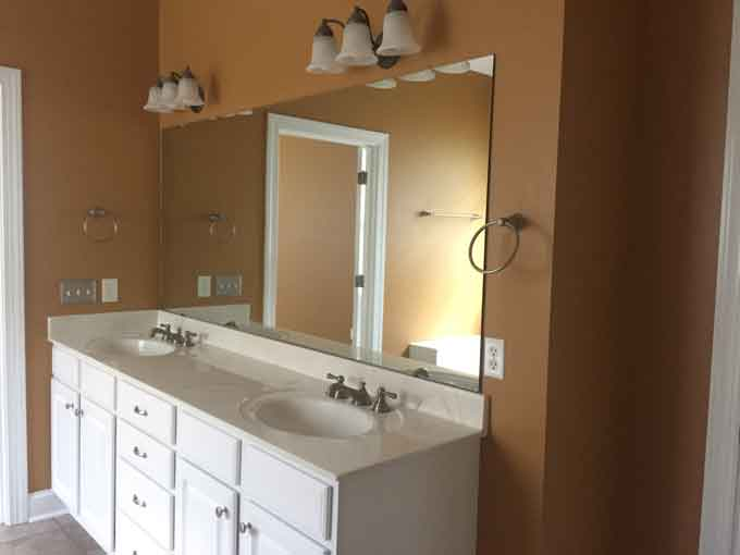 A bathroom with two sinks, a large mirror and brown wall color