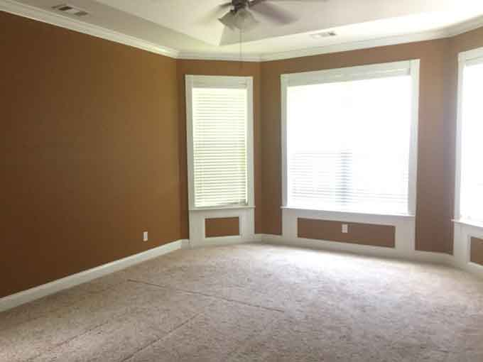 A bedroom with brown walls