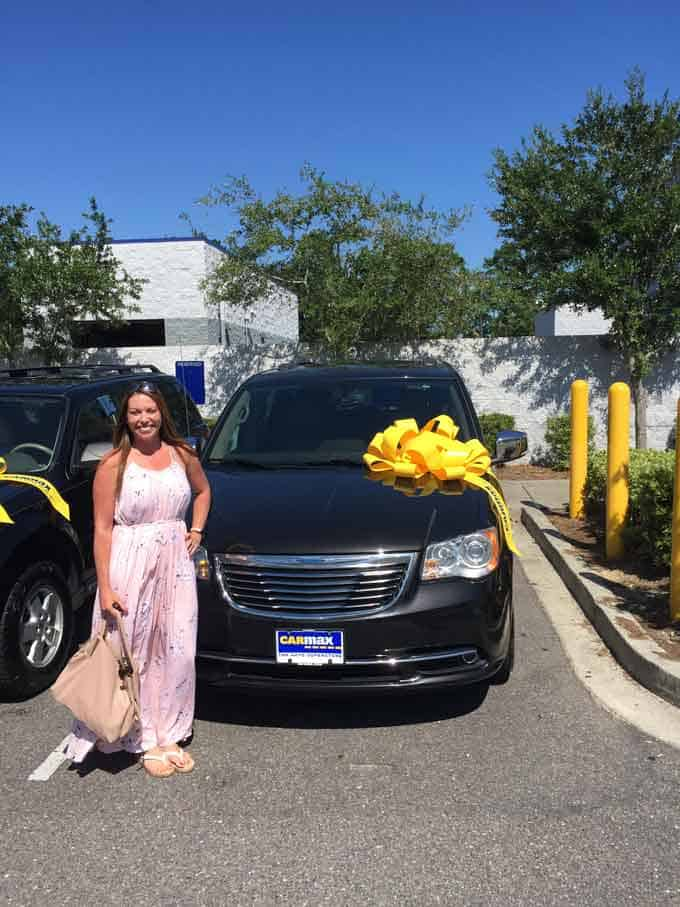 A woman in a dress standing in front of a new minivan with a yellow bow on the minivan