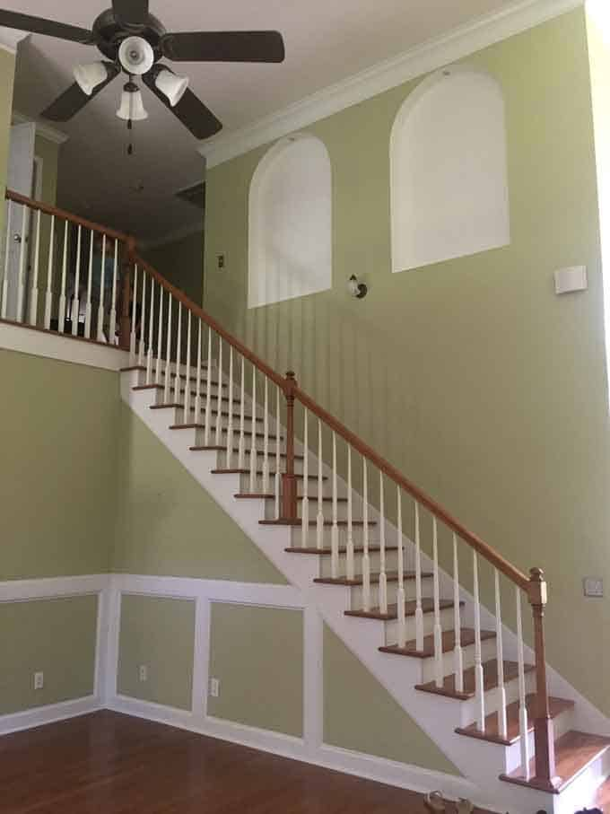 A before picture of a staircase and light green wall paint