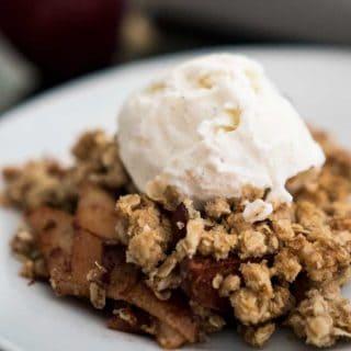 apple crisp on white plate with vanilla ice cream on top
