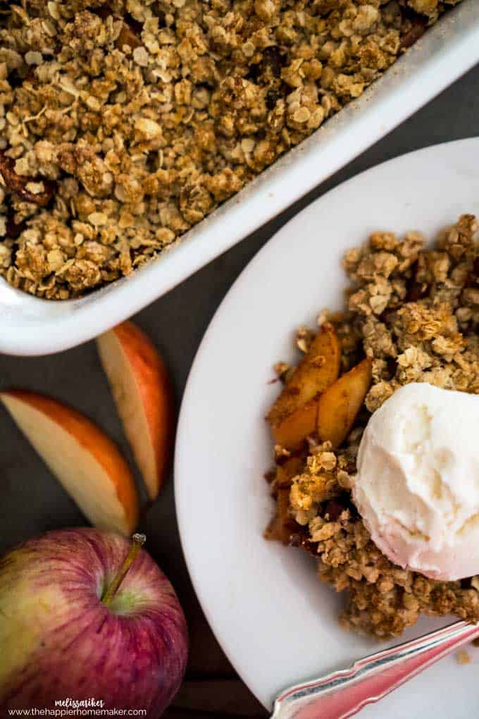 A plate and baking tray filled with apple oatmeal crisp with sliced apples and ice cream as garnish