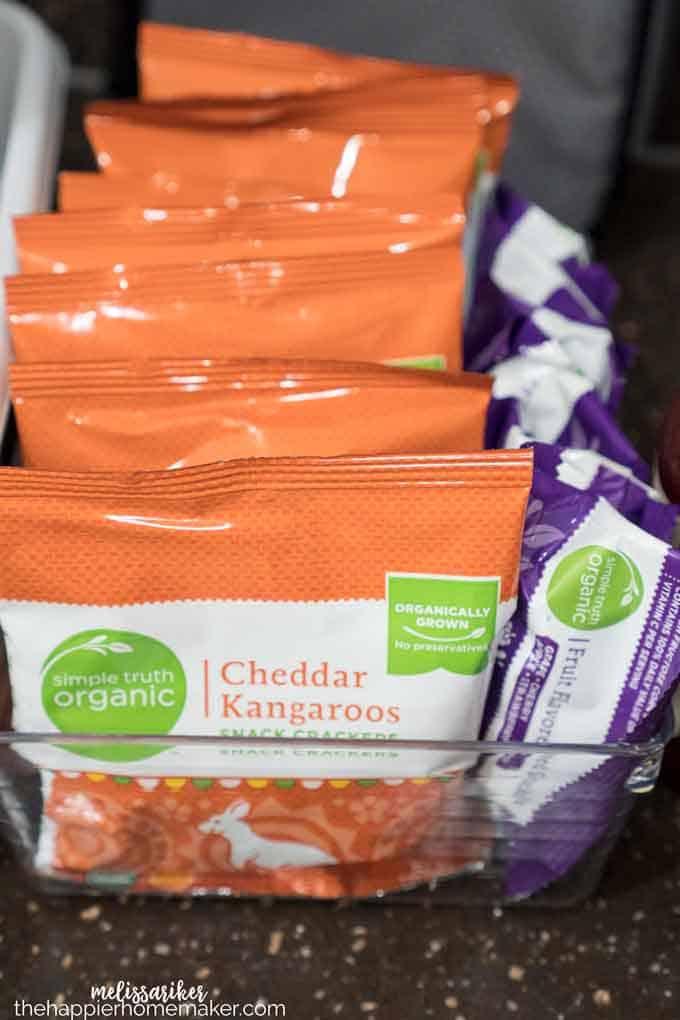 A plastic organizing bin with cheddar snacks inside