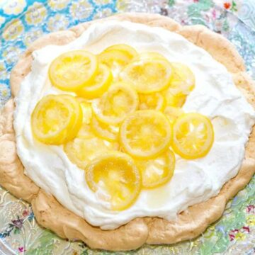 pavlova topped with whipped cream and candies lemons