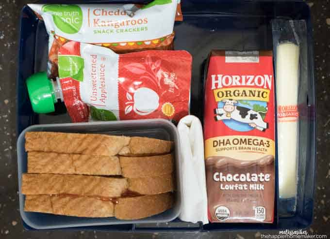 An above picture of a lunchbox with chocolate milk, sandwich and snacks